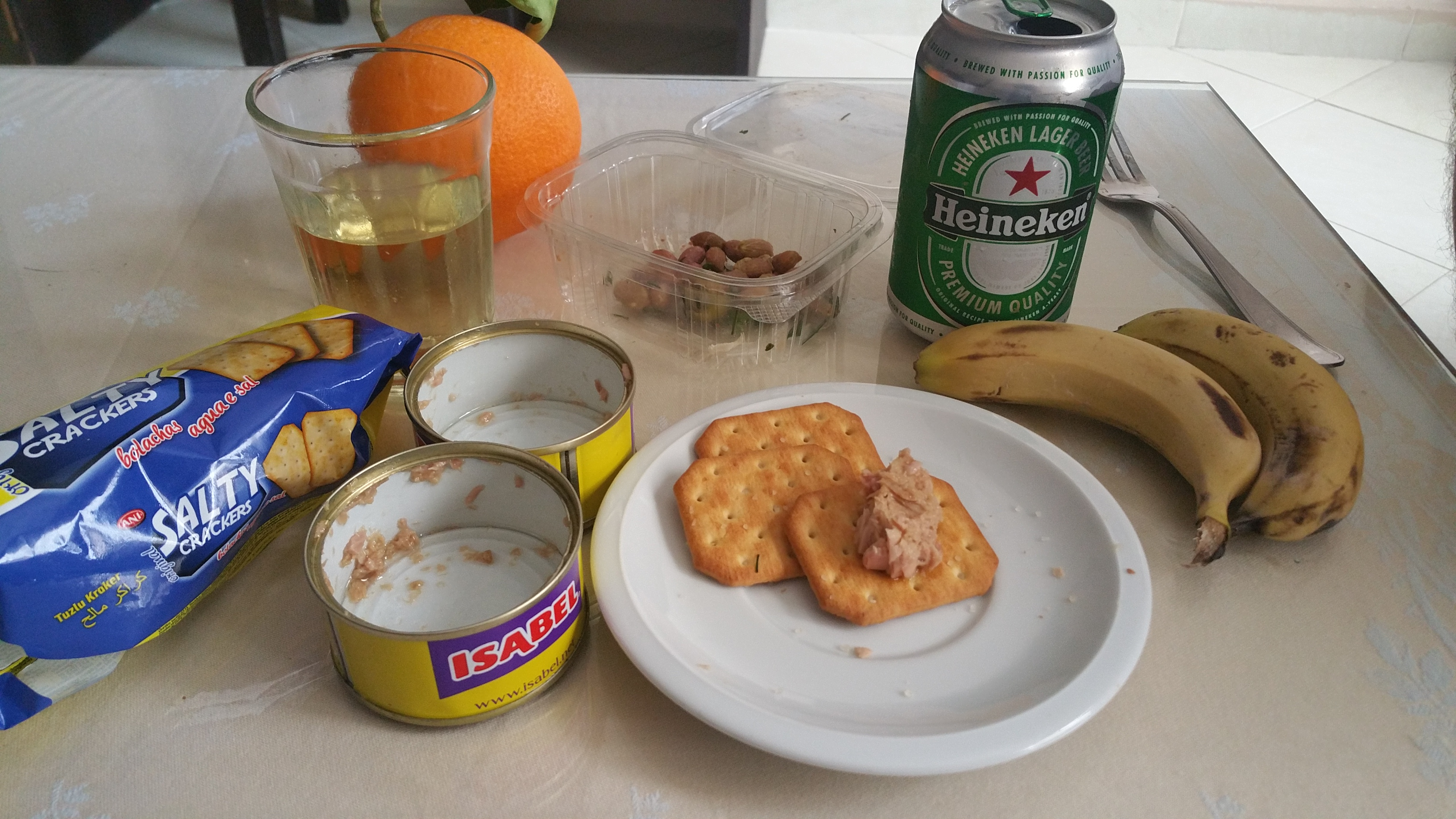 travelling larder, crackers, canned tuna, olives, bananas and an orange